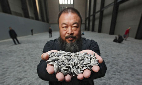 Click the image for a view of: Chinese artist Ai Weiwei at his current exhibition of 100 million ceramic seeds at the Tate Modern