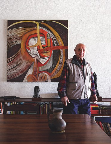 Click the image for a view of: Egon Guenther stands next to a Cecil Skotnes wood panel in the wing of the house and former gallery where he lived in Johannesburg