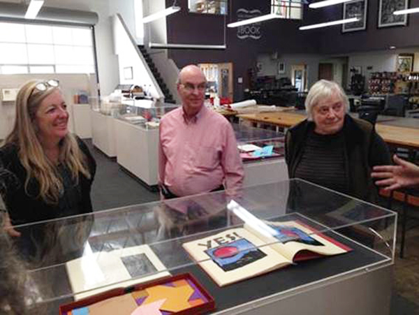 Click the image for a view of: Mary Austin, Jack and Claire Van Vliet at the Center for the Book, SF, with the retrospective exhibition for the Janus Press on display